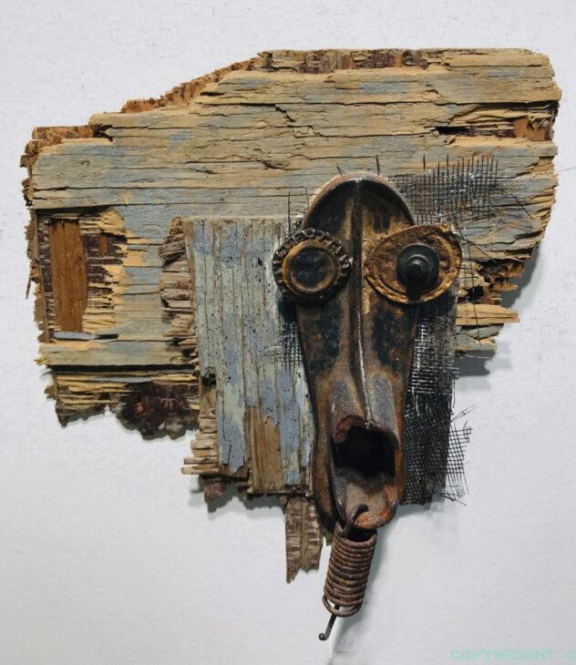art-sculpture-masque-objets recyclé-visage de fer sur fond de bois-Hélène Patenaude